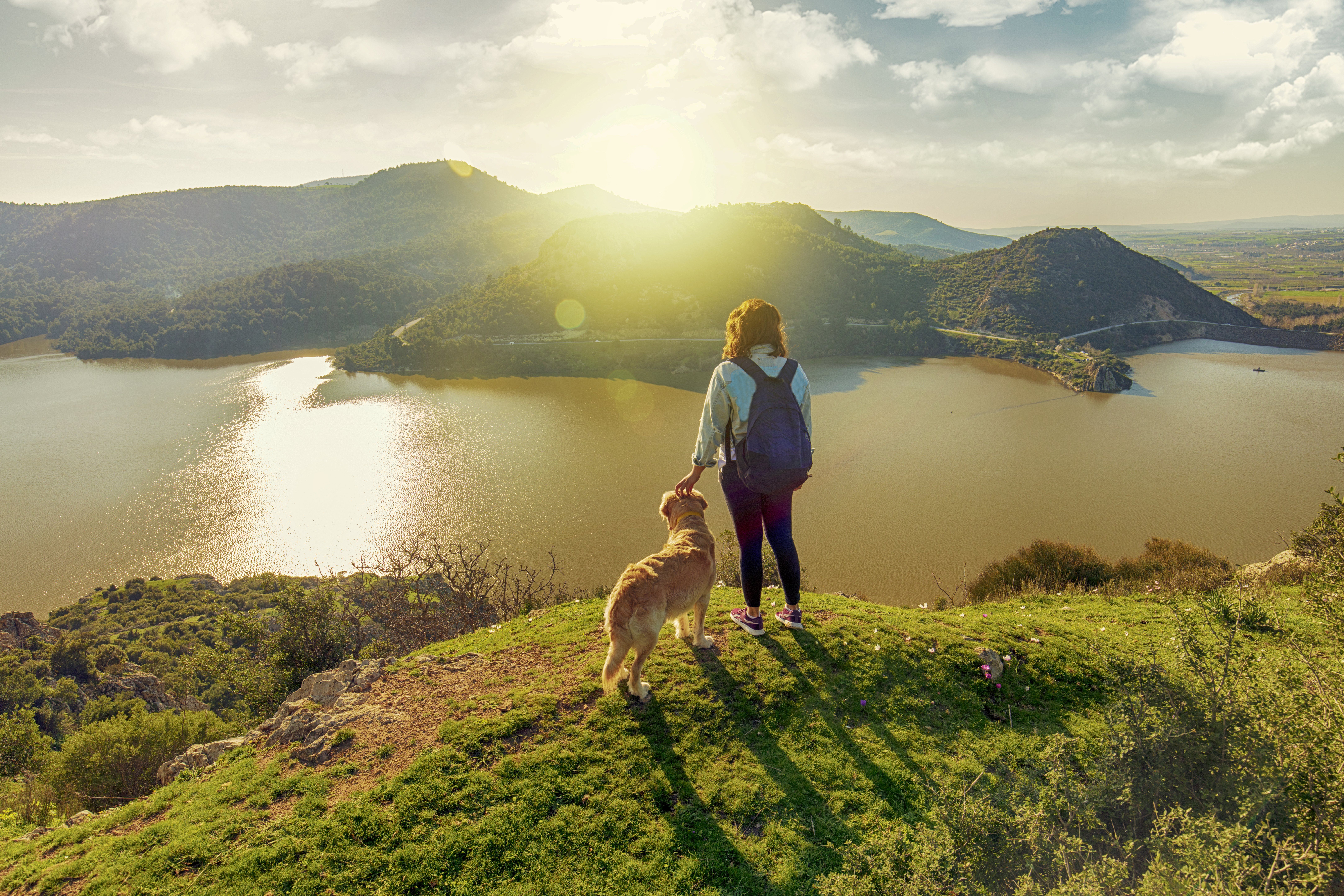 young woman trekking with the dog on mountains